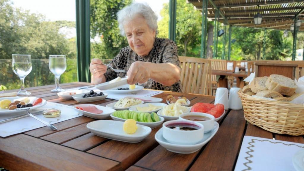 Una mujer de la tercera edad (anciana) come una comida nutritiva