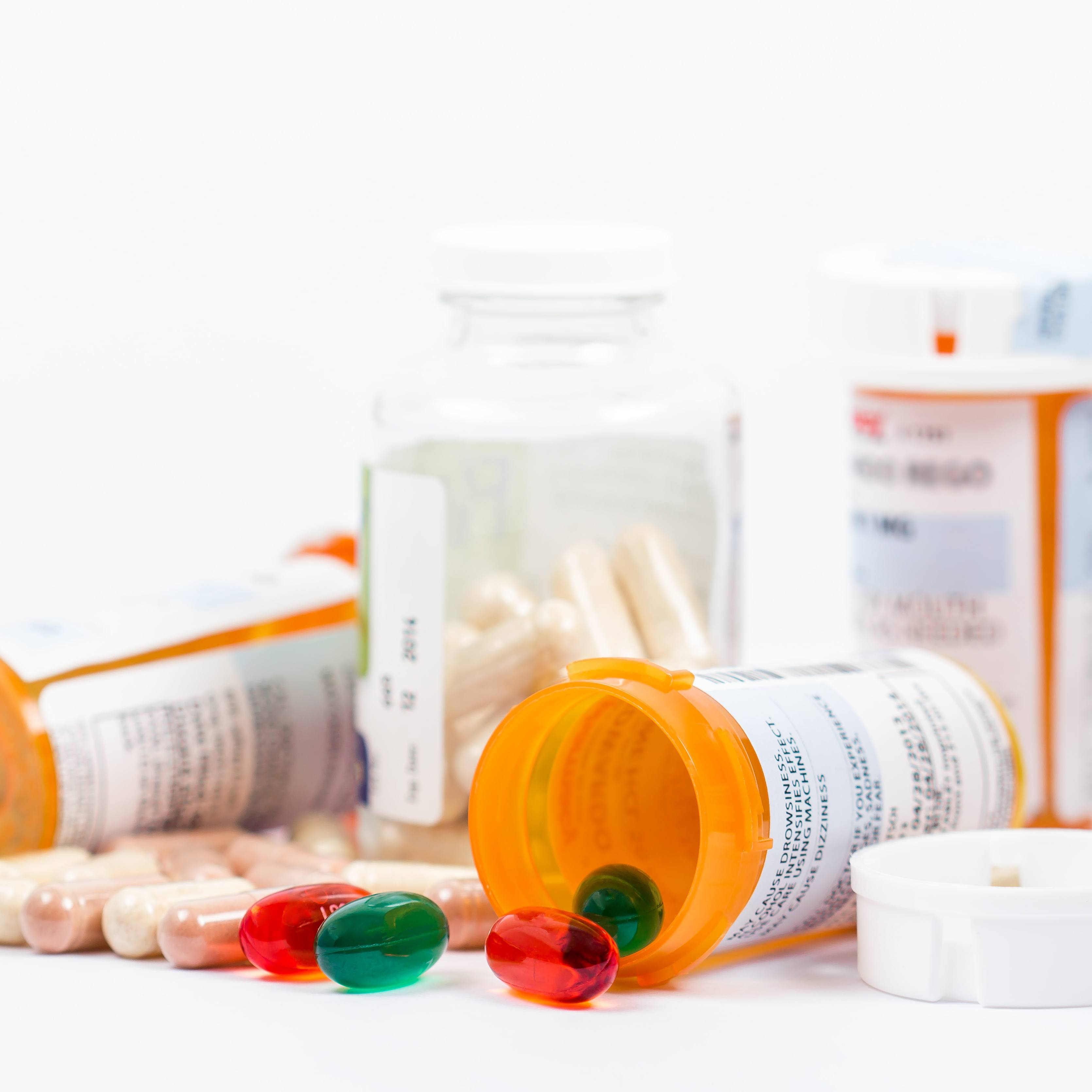 several prescription medicine bottles, some lying on their sides with pills and capsules spilling out
