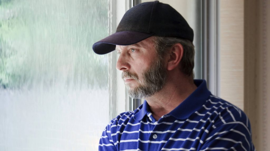 Un hombre de mediana edad con una gorra de béisbol mira triste, pensativo, preocupado y deprimido por la ventana