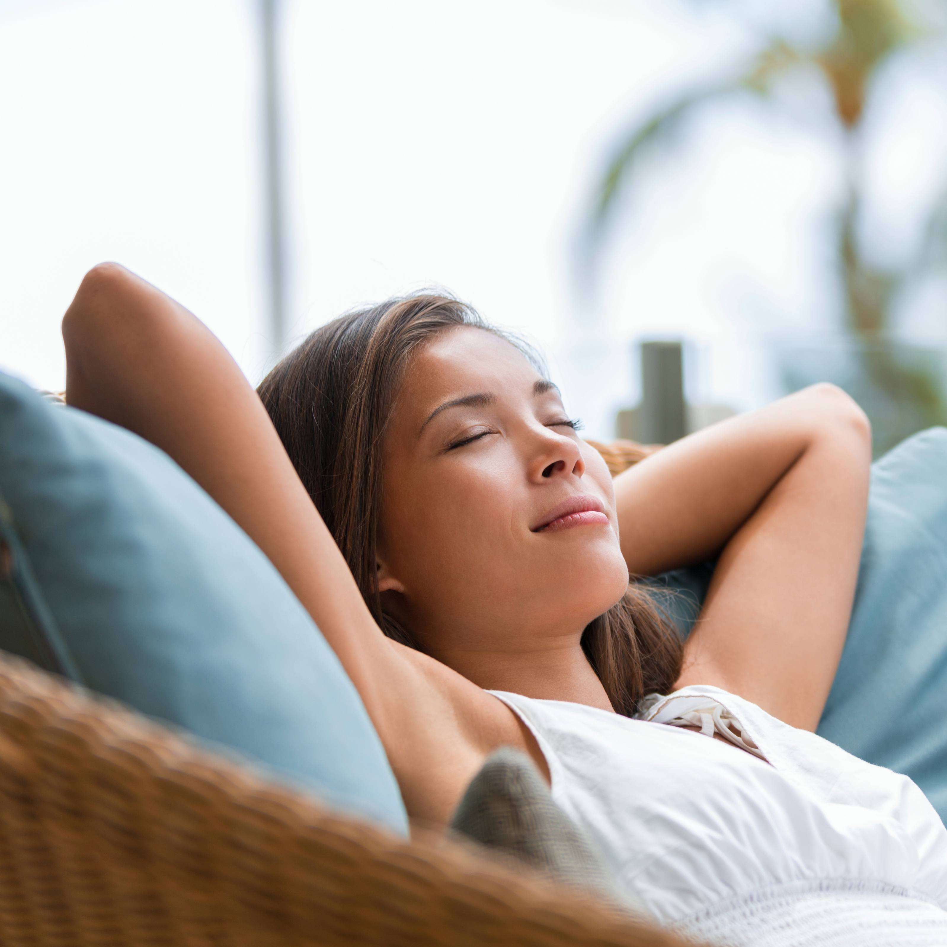 a young woman resting, sleeping, napping outside on a wicker couch