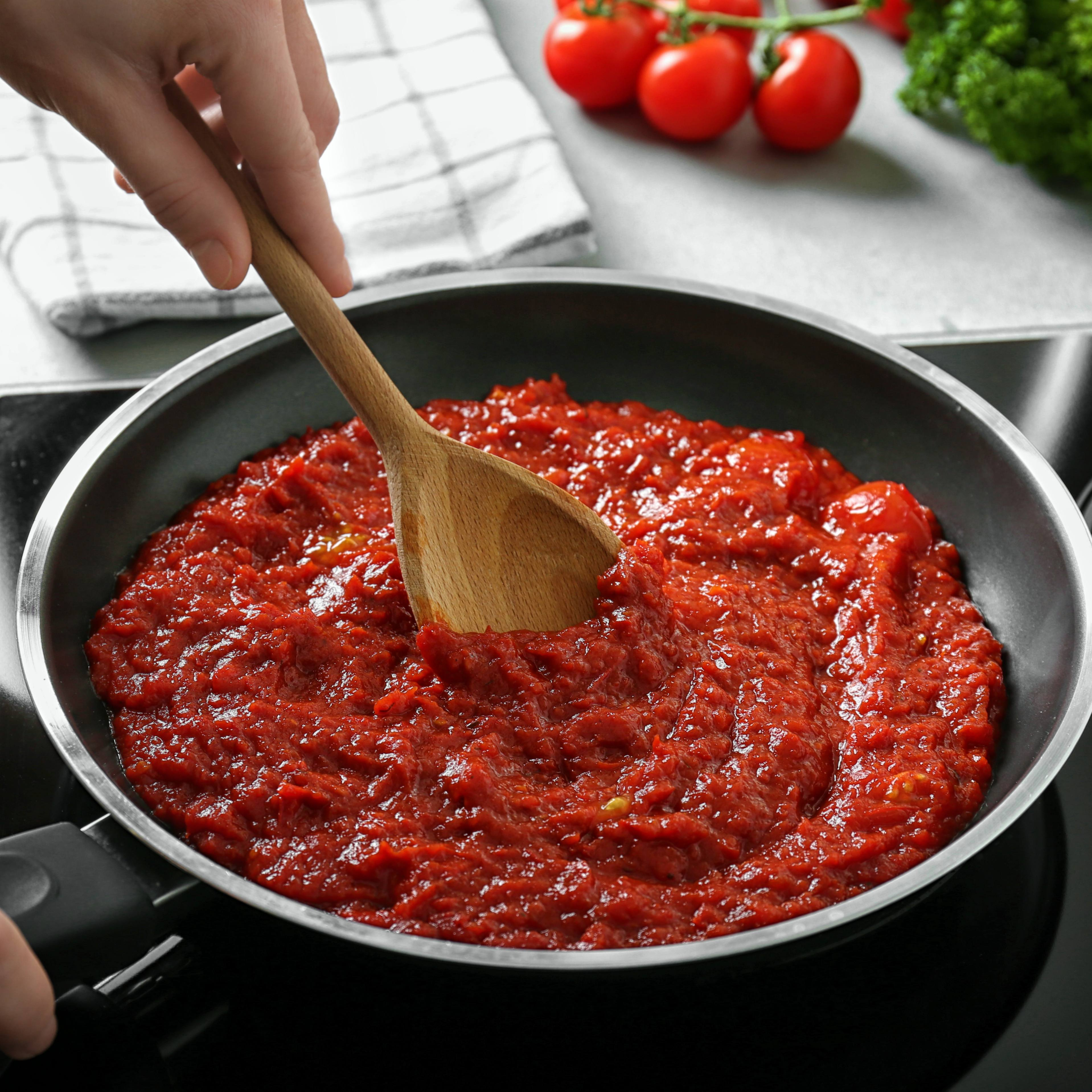 close up of a large frying pan with person at the stove cooking, stirring a red spaghetti or marinara sauce