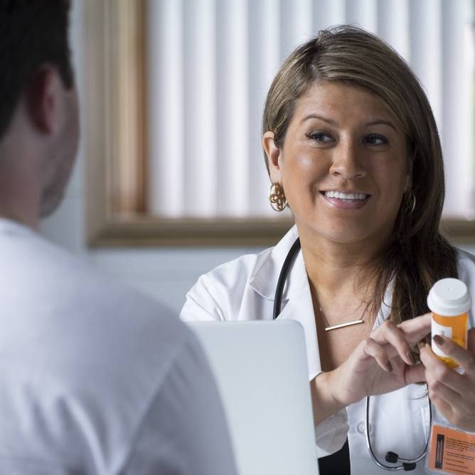 Hispanic woman doctor talking to male patient with prescription bottle