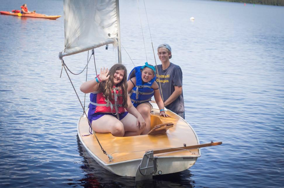 children from Camp Wabi in a sailboat