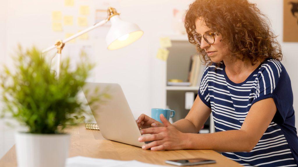 Mujer de mediana edad frente a la pantalla de una computadora móvil y con aspecto de mucha concentración