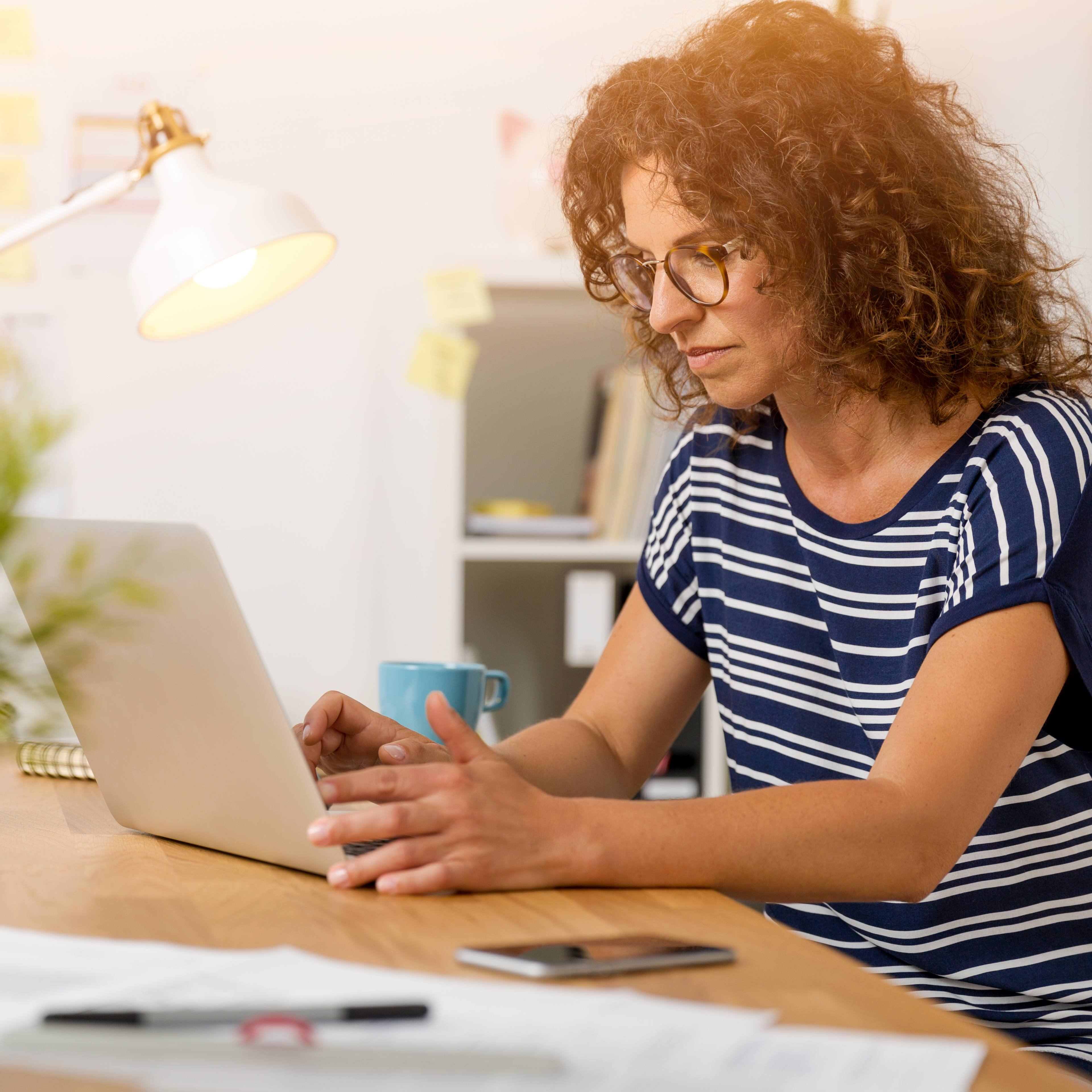 a middle-aged woman looking at a laptop screen, with a concerned look on her face