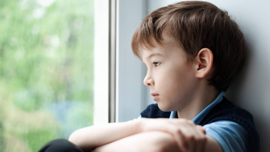 a sad, depressed, upset, unhappy little boy sitting near a window and looking out