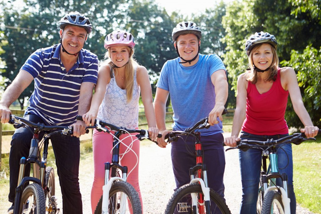 a family on bicycles - father, mother and teenage daughter and son, all wearing helmets