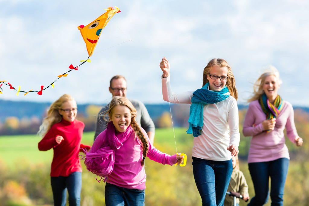 a family - parents and young children - running outside, flying a kite, laughing