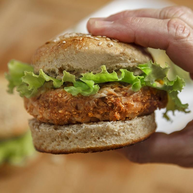 closeup of a person holding a turkey burger with lettuce