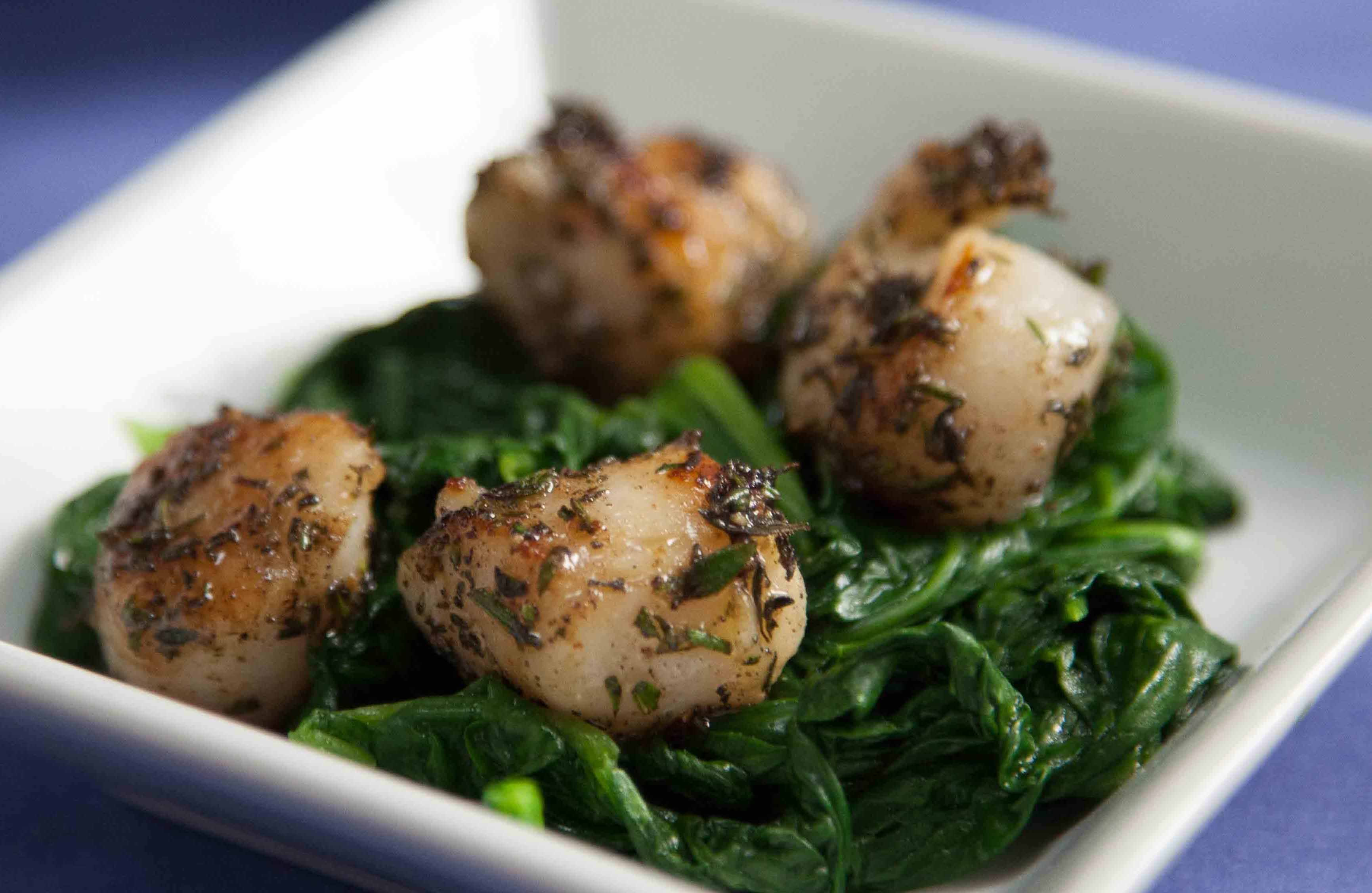 a white bowl with seared scallops and green vegetables