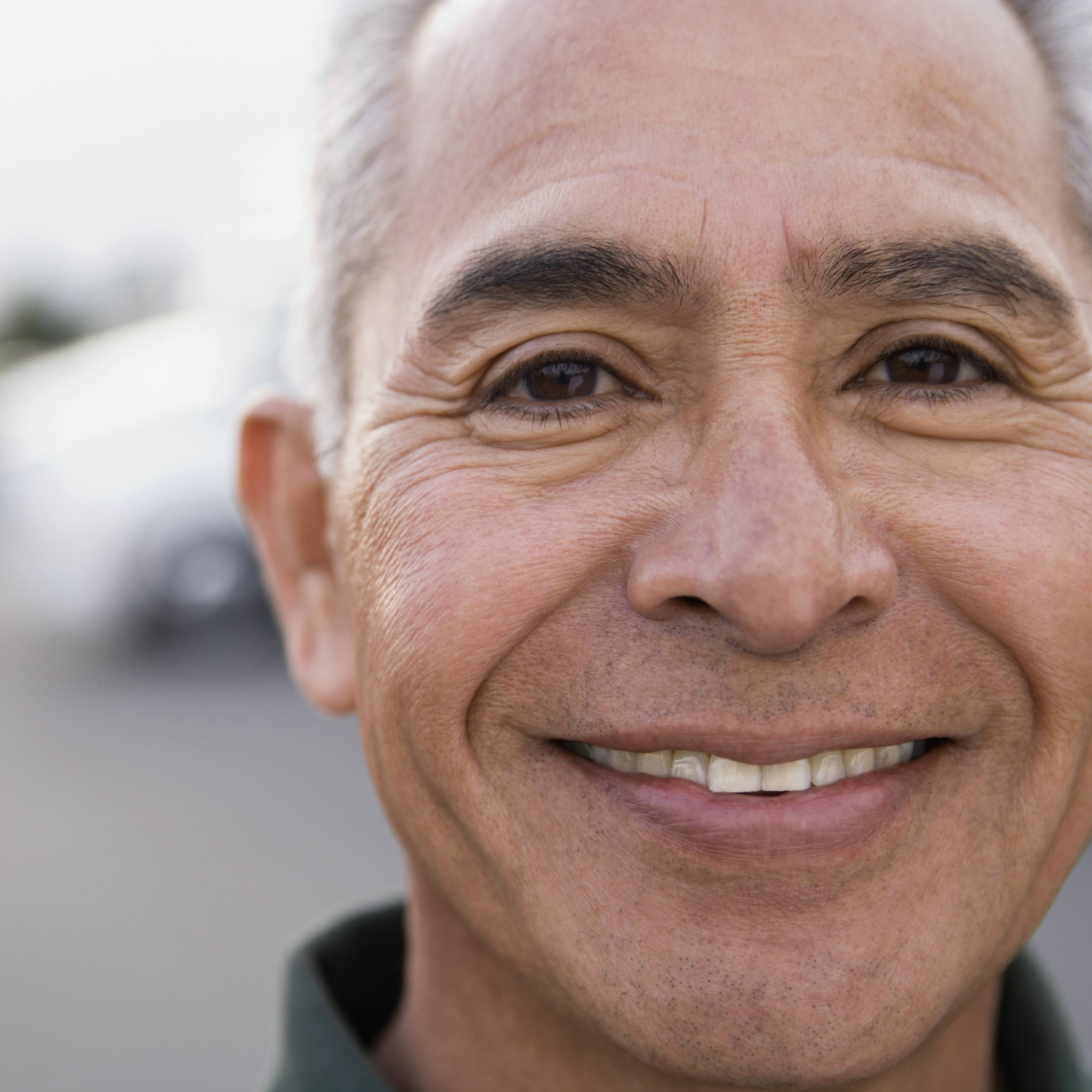 a close-up of a smiling middle-aged man smiling