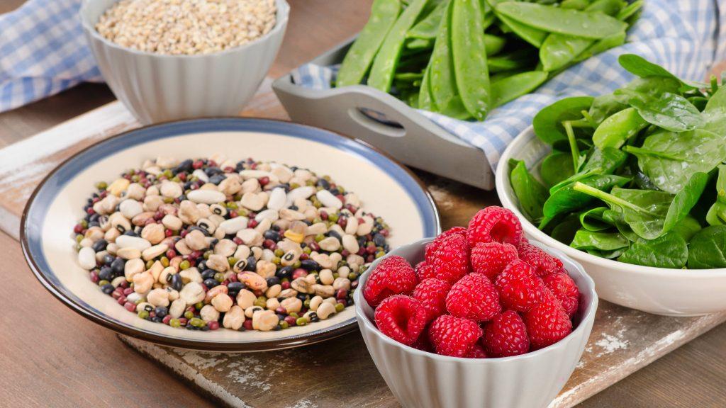 Un surtido de alimentos con alto contenido de fibra, como frutas, verduras, cereales integrales y legumbres, en diferentes tazones y sobre una superficie de madera