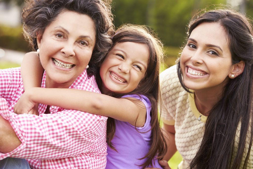 a close-up of three generations - grandmother, daughter and granddaughter - outdoors, smiling, hugging