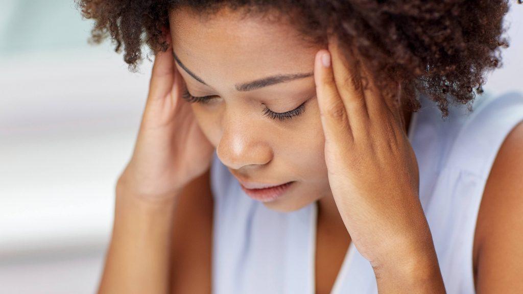 Una mujer joven con la mirada baja y cara de tristeza se sostiene la cabeza porque le duele