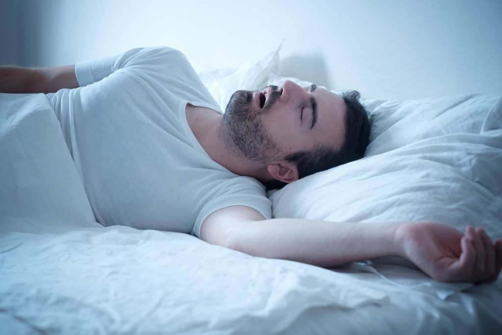 a man lying on his back in bed, asleep, mouth open, snoring