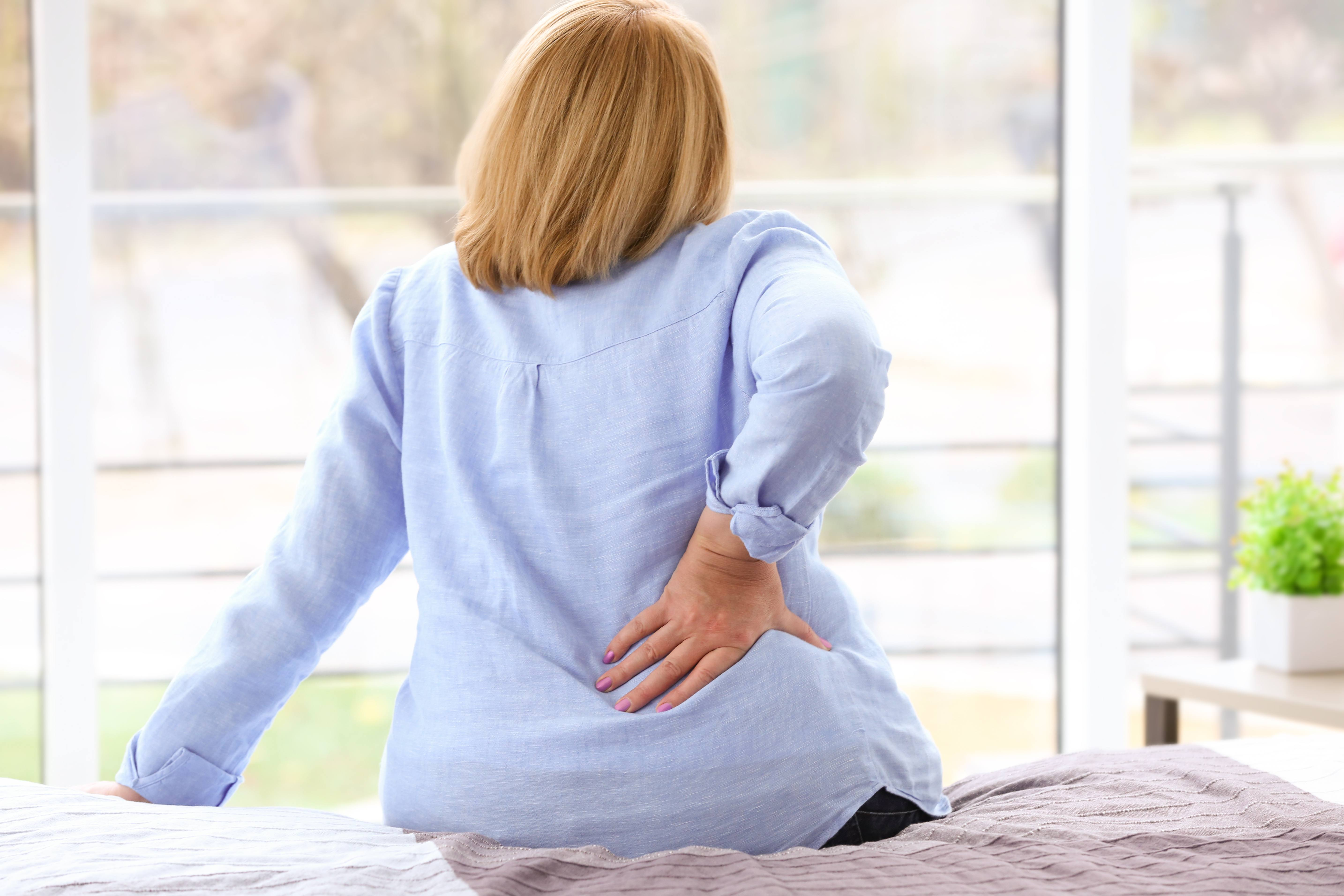 a middle-aged woman sitting on a bed with her hand on her back revealing pain