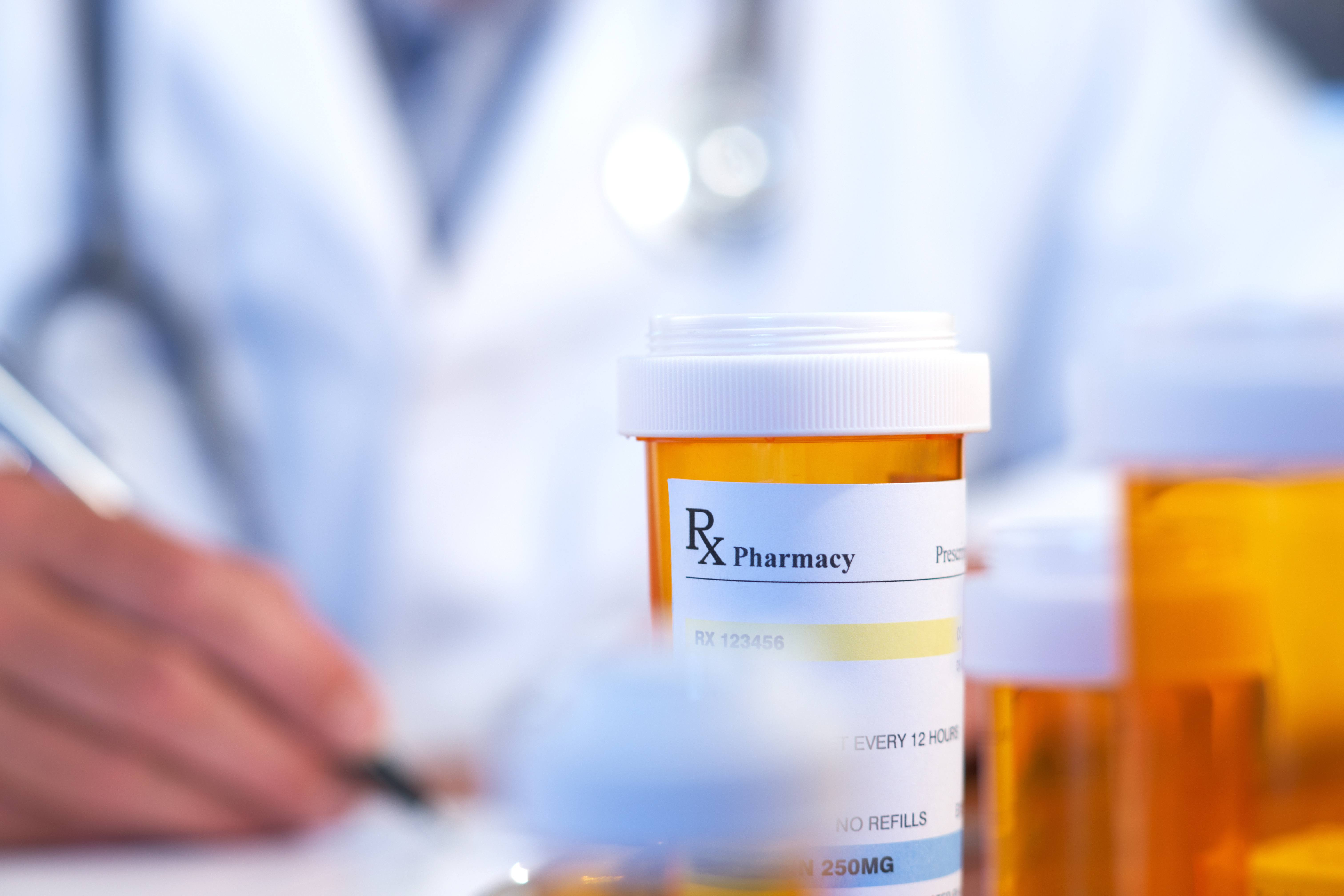 a prescription medicine pill bottle with a health care provider in the background