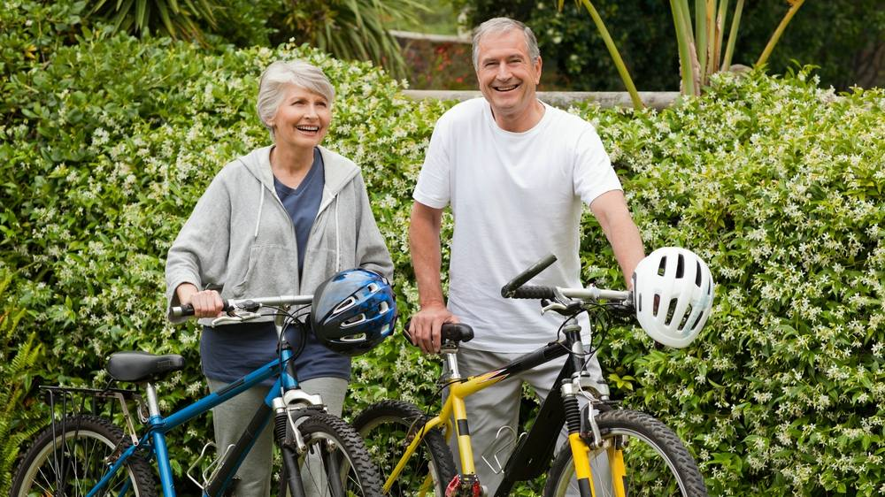a happy looking senior couple walking with their bicycles