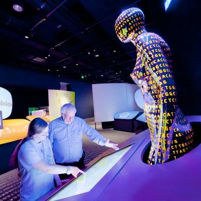 two people looking at an exhibit highlighting genomic technology