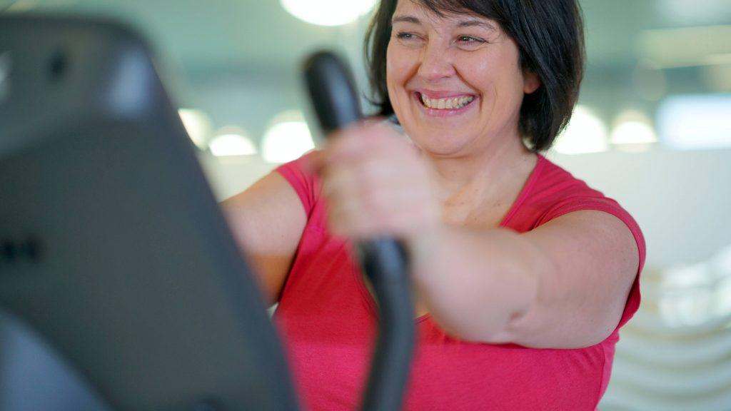 Una mujer muy gorda está en el gimnasio haciendo ejercicios aeróbicos en una bicicleta