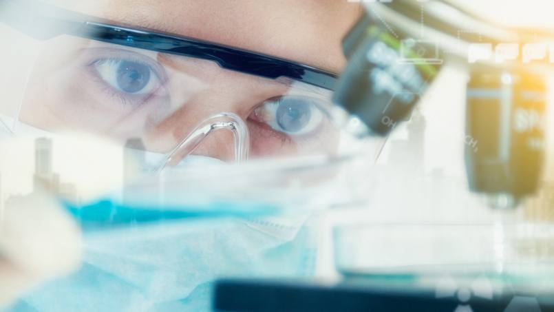 closeup of a researcher wearing protective glasses while looking into a microscope in a lab