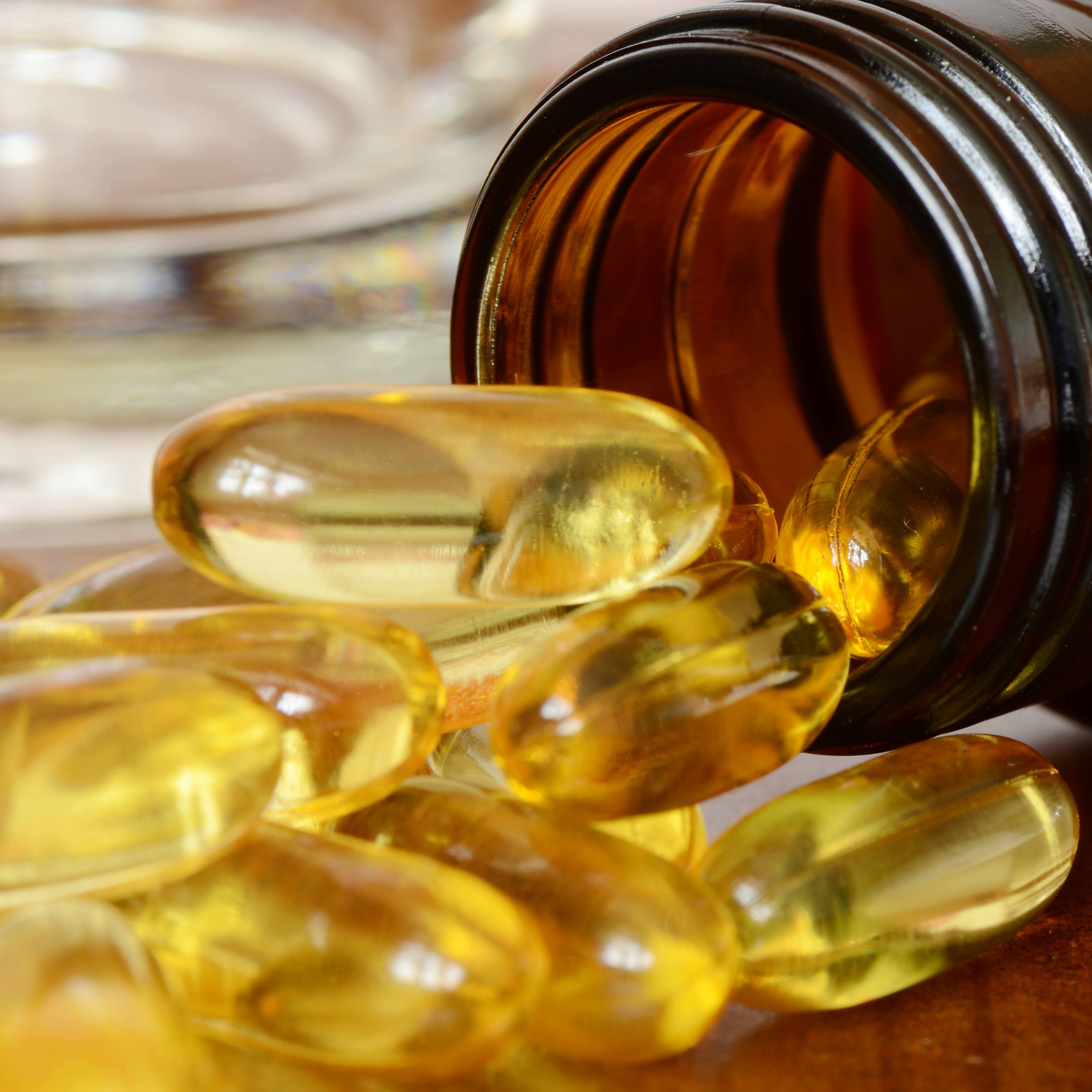 soft gelatin dietary supplement oil capsules spilling out of a bottle