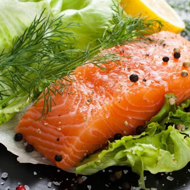 a salmon fillet, rich in omega 3 fish oil, aromatic spices and lemon on fresh lettuce leaves on black wooden background