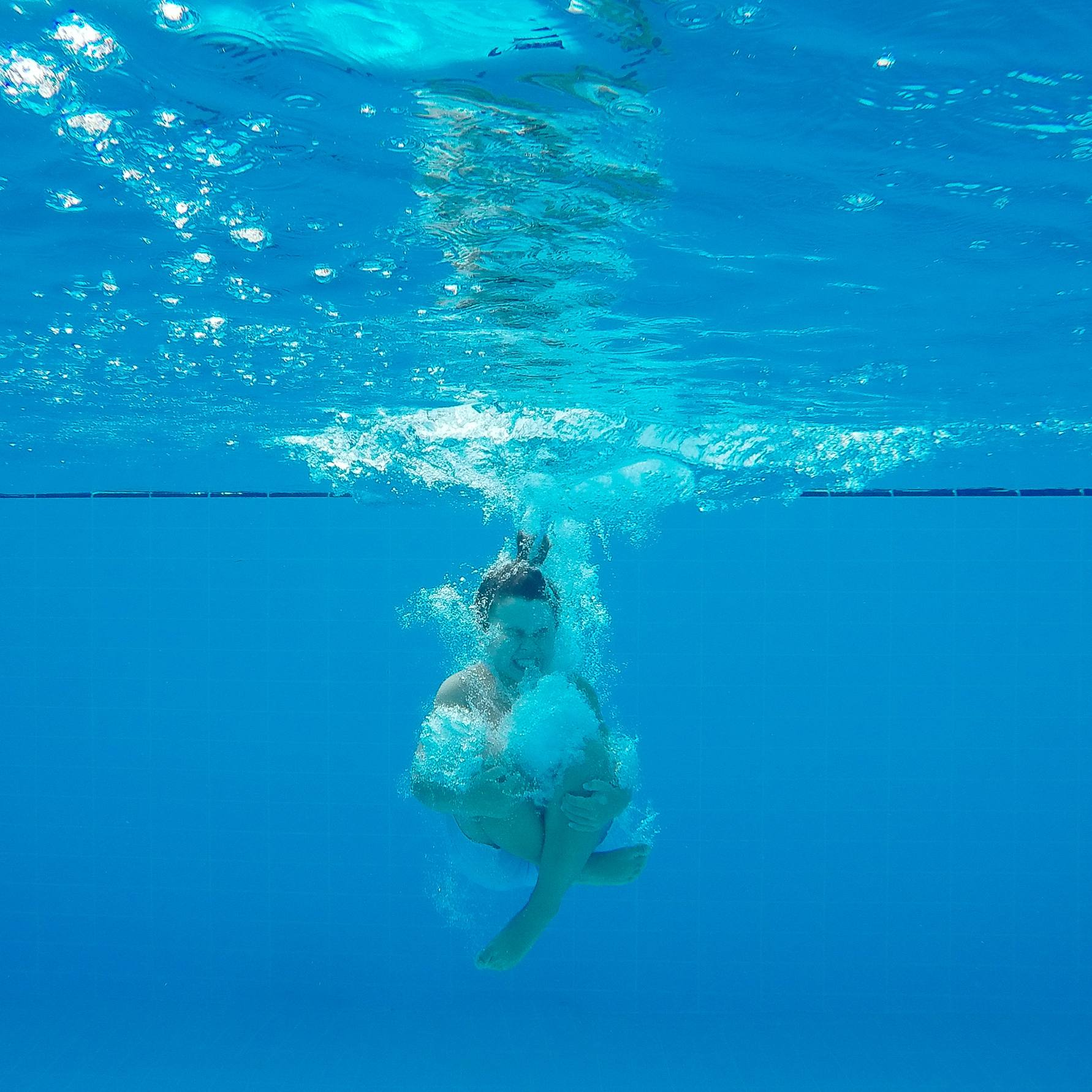 a little boy jumping or splashing into the water, underwater of a swimming pool
