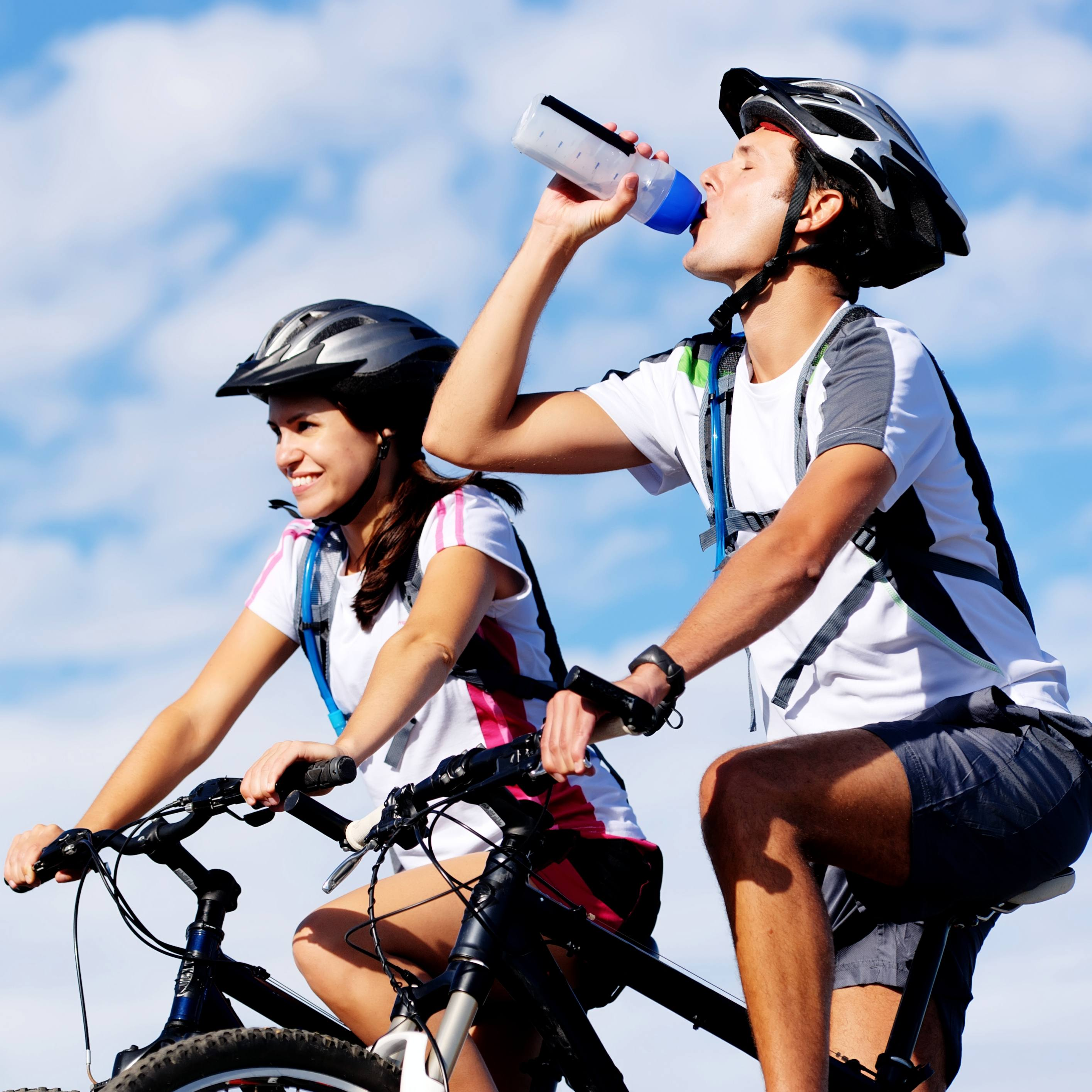 a man and a woman on their bicycles, wearing helmets and enjoying the outdoors with blue sky in the background and the man is thirsty, drinking water to stay hydrated