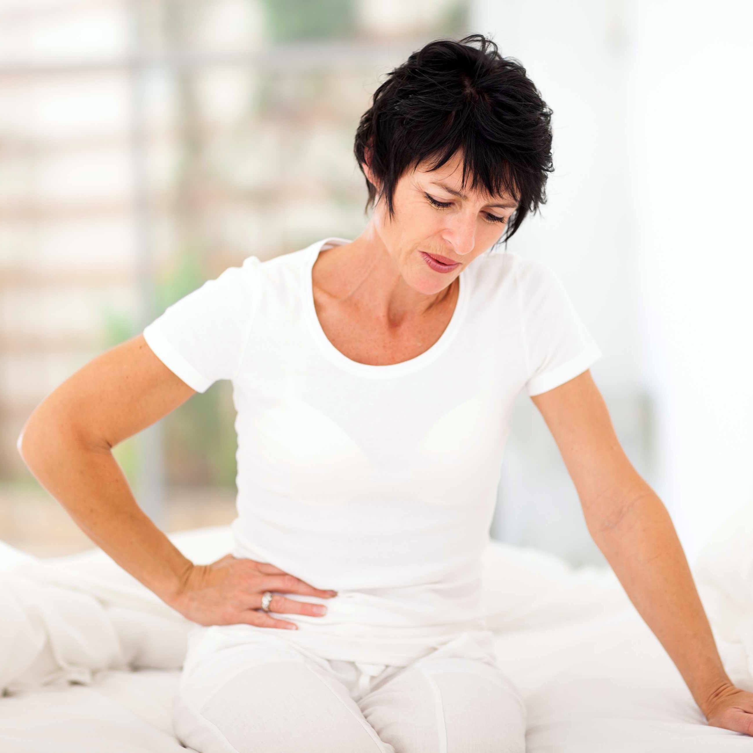 woman having stomach aches, cramps and pain - menstruation