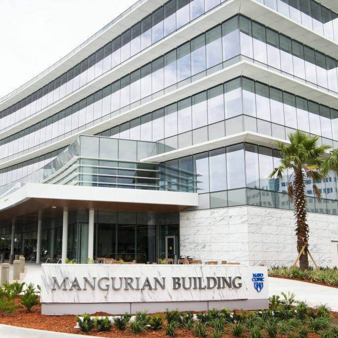 a closeup of the Mangurian Building and sign on the Florida campus