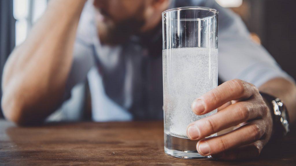 Un hombre con resaca sostiene un vaso de agua con analgésicos