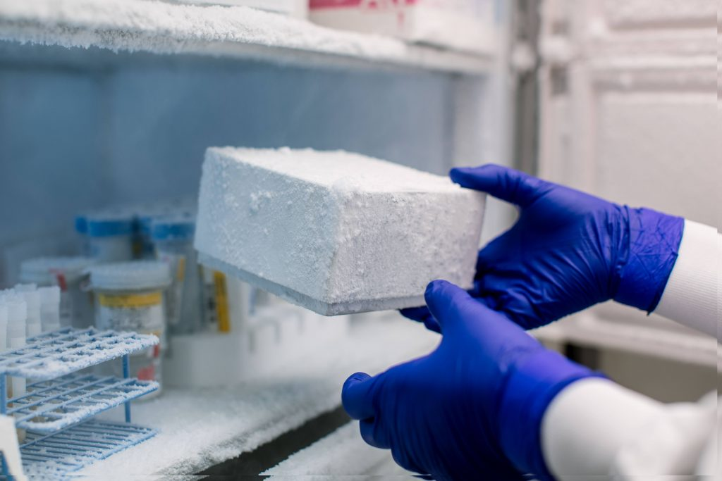 Research technologist removing frozen lab specimens from freezer