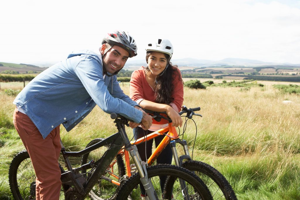 Young couple cycling In countryside