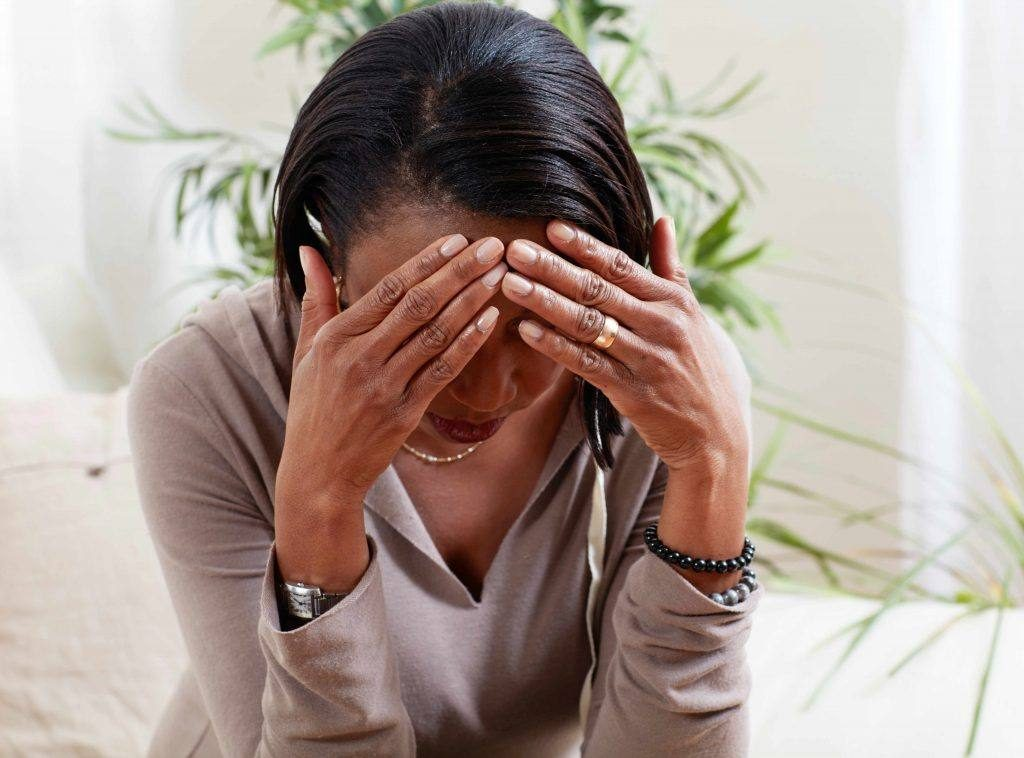an African-American woman holding her head in her hands looking tired, worried or maybe with a headache or migraine