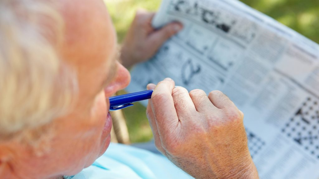 an elderly man, senior citizen sitting outdoors doing the crossword puzzle in the newspaper, perhaps to exercise his brain and his memory, keeping his mind health