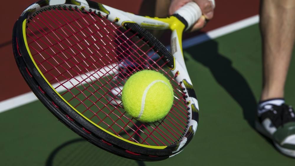 a tennis player balancing a tennis ball on a tennis racket