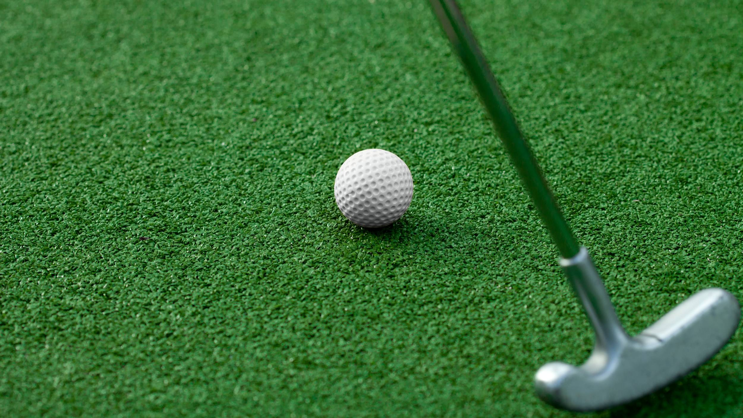 a golf ball on a putting green with someone holding a putter close by ready to tap the ball