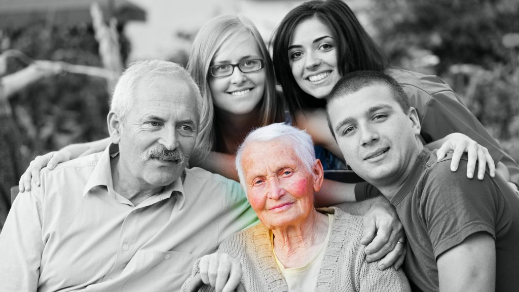 a black and white photo of family members gathered around an elderly woman who is highlighted in the picture, looking a little bit sad and weak, perhaps sick and maybe having dementia or Alzheimer's