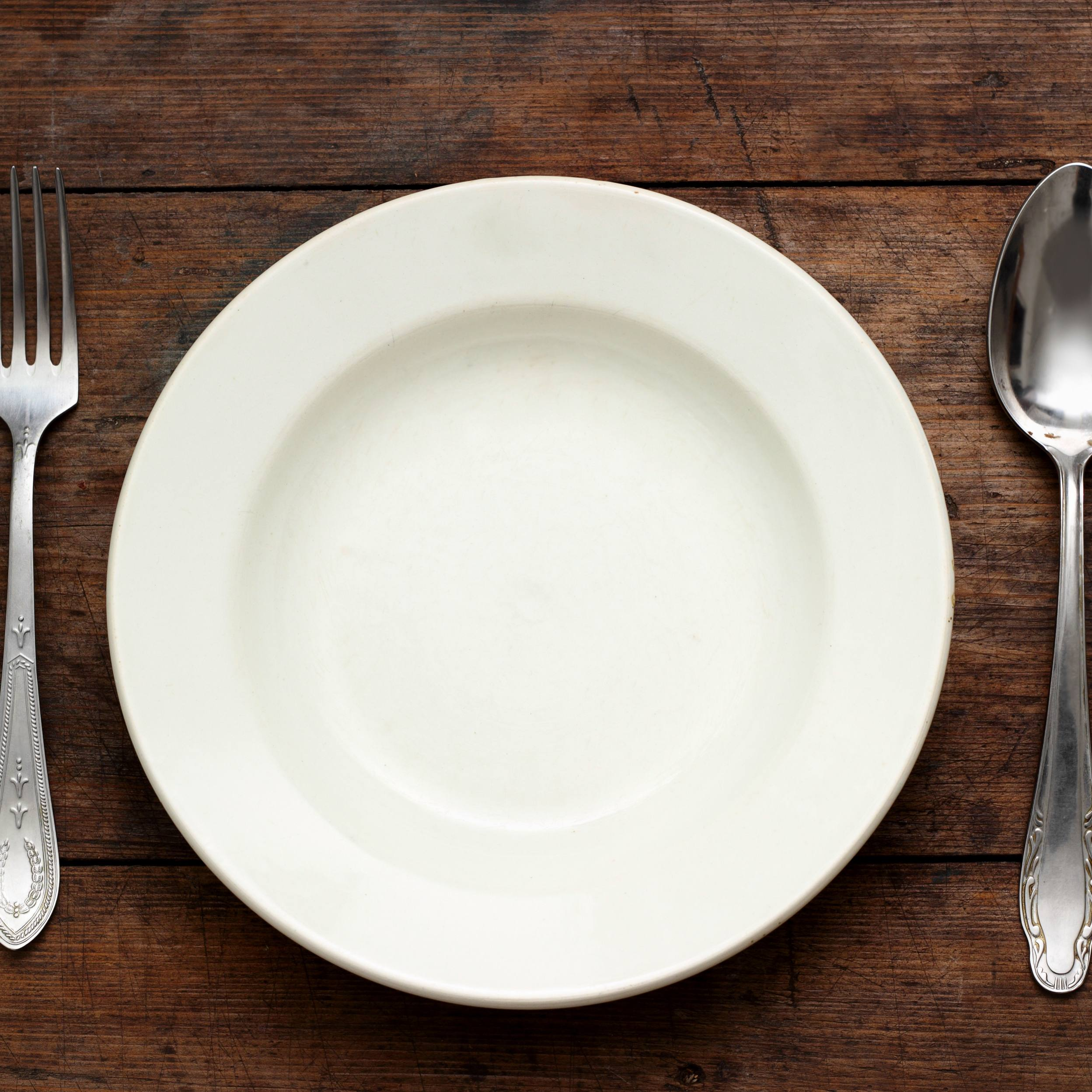 Empty plate with spoon and fork on wooden background