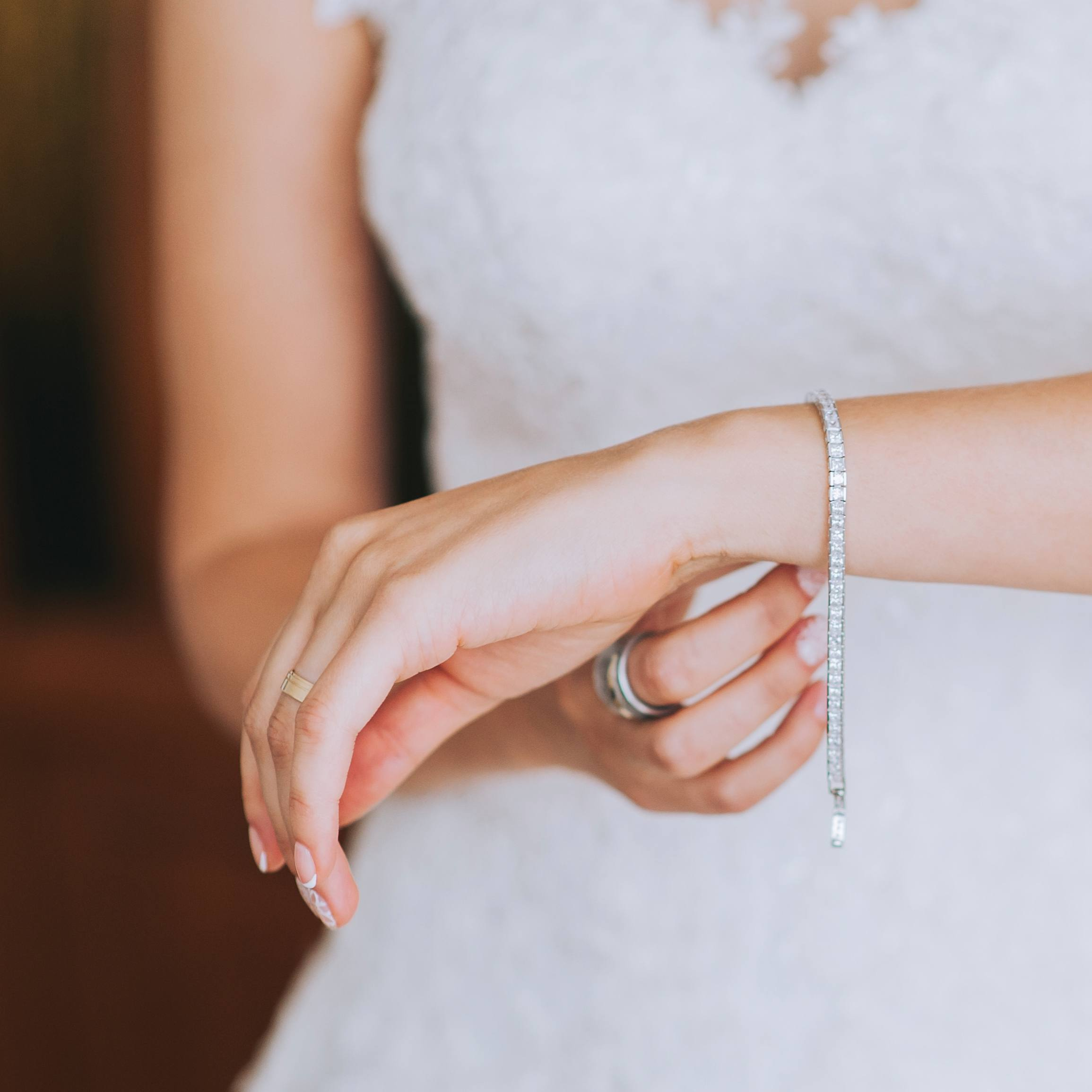 a bride in a wedding dress putting on her jewelry, a diamond bracelet on her wrist
