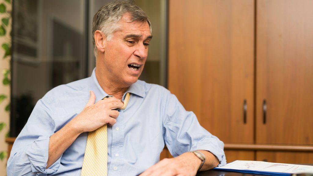 Un hombre con una camisa azul se afloja la corbata por el calor y se muestra desasosegado o enfermo, como si tuviera fiebre o dolor del pecho