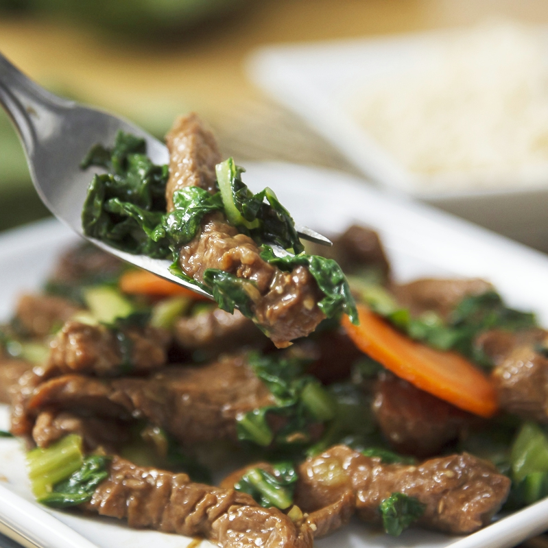 Brown-sugared pork tenderloin stir-fry on a plate with someone holding a fork