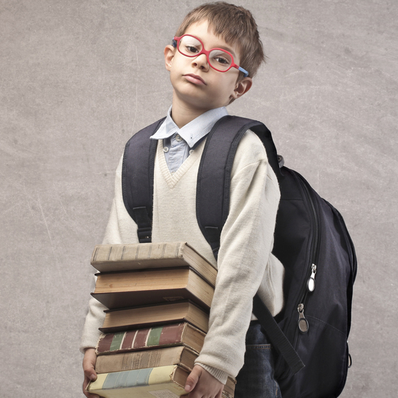 A young school student holds a stack of books wearing a large backpack.