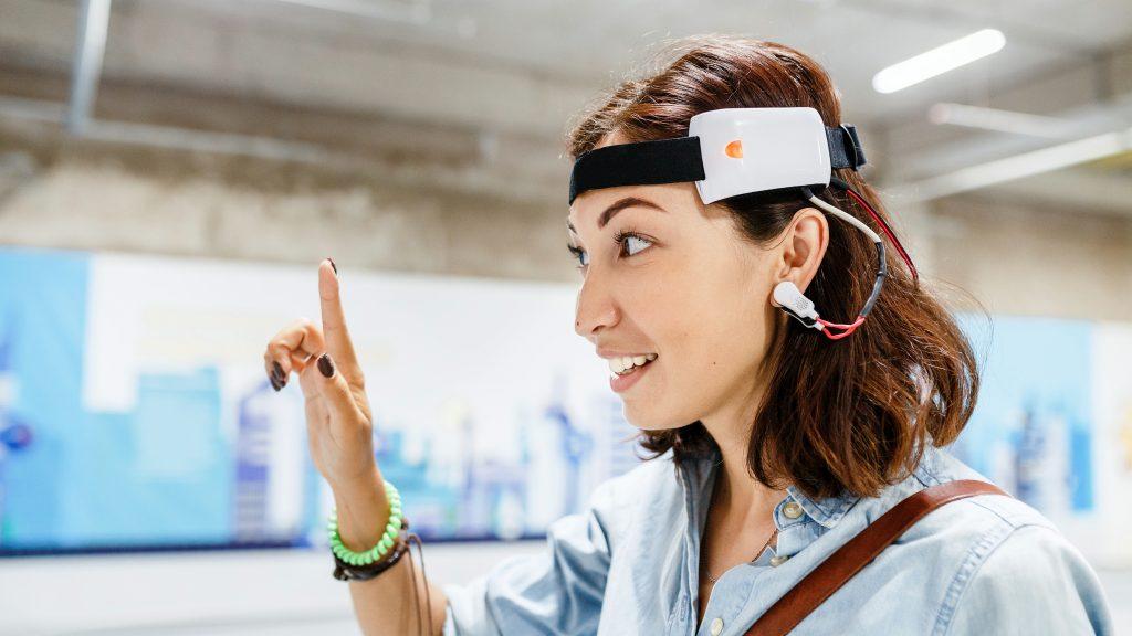 Mujer con un sensor digital conectado en la oreja para leer los impulsos cerebrales