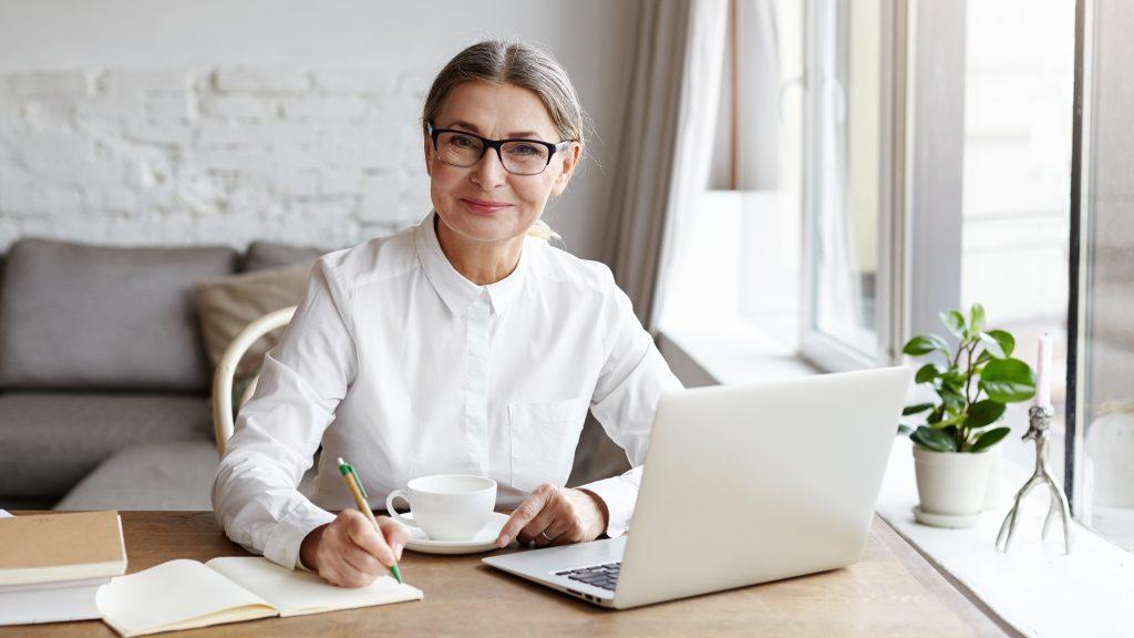 Una mujer mayor sentada al escritorio de una habitación soleada sonríe frente a un computador portátil mientras sostiene una taza y escribe un diario