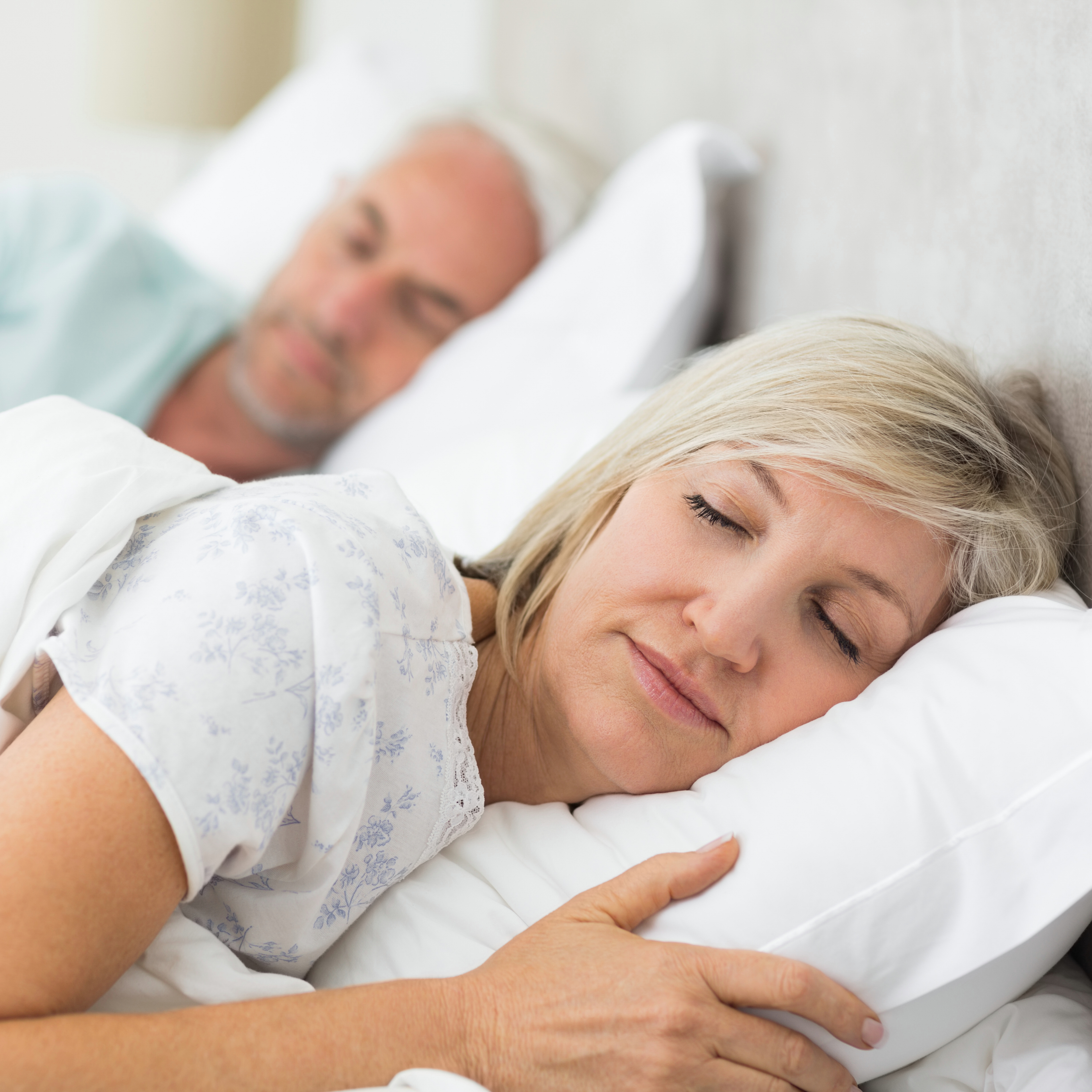 a middle-aged couple sleeping in bed
