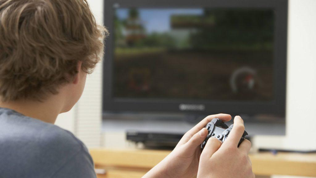 Un muchacho adolescente sostiene la palanca de mando del videojuego mientras mira la pantalla del televisor