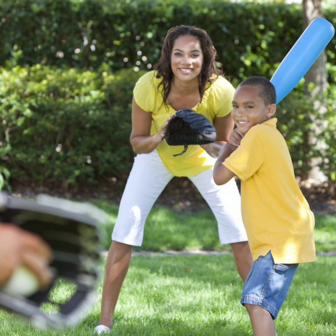 a family playing baseball or whiffle ball outside