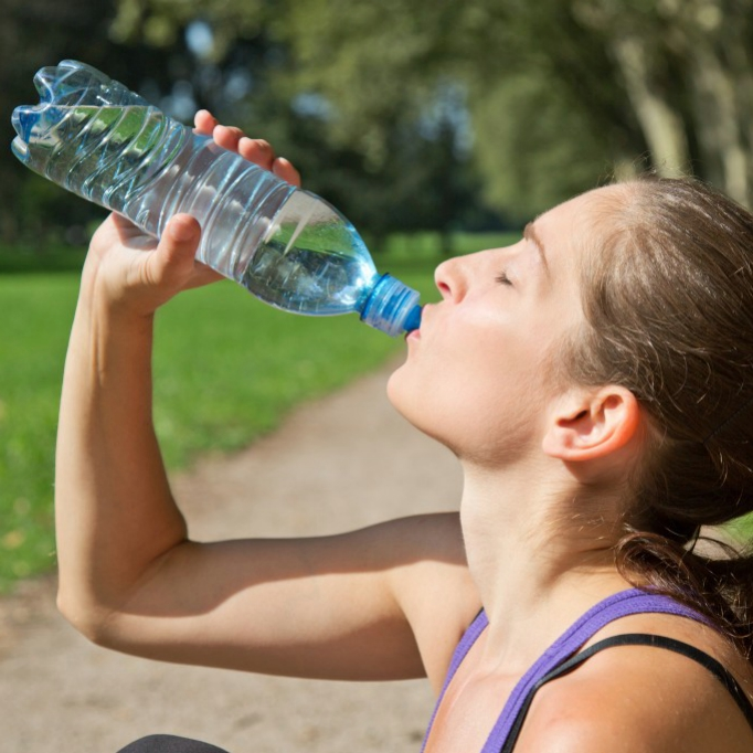 woman drinking out of a water bottle after exercising - staying hydrated